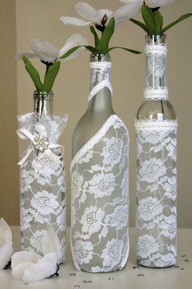 Garrafas de vidro como vaso cobertas por pedaços de tecido de renda