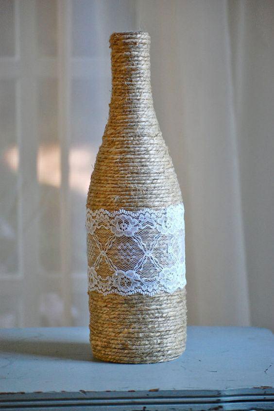 Garrafa coberta completamente por palha e com um pedaço pequeno de tecido de renda