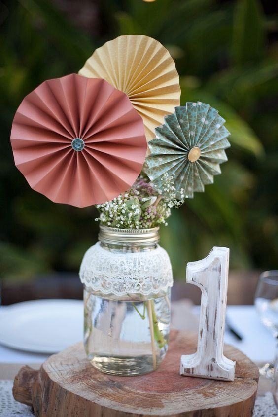 Vaso decorado com flores e leques, coberto por tecido de renda na parte superior do frasco