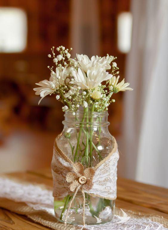 Vaso feito com frasco de vidro levando um tecido de juta com renda e botão de flor.