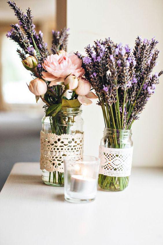 Frascos com flores coloridas e renda