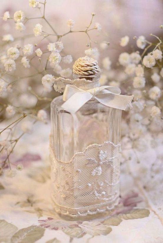Decoração delicada de uma garrafa de vidro com tecido de renda e laço branco