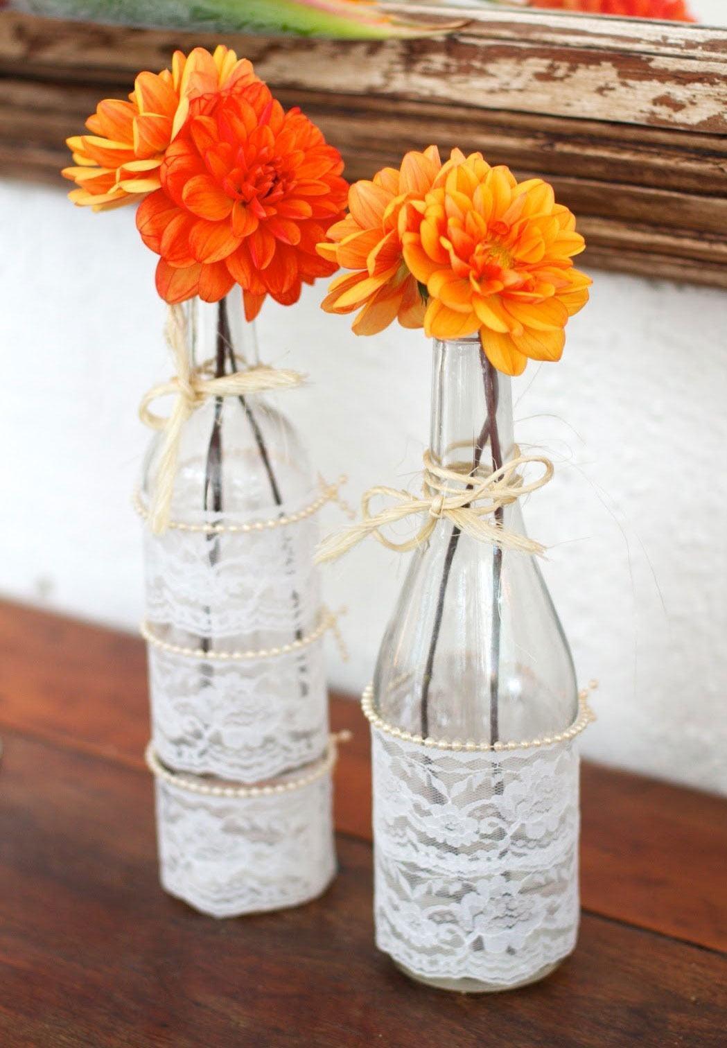 Garrafas com flores coloridas, tecido de juta, pequenas pérolas e laços de palha