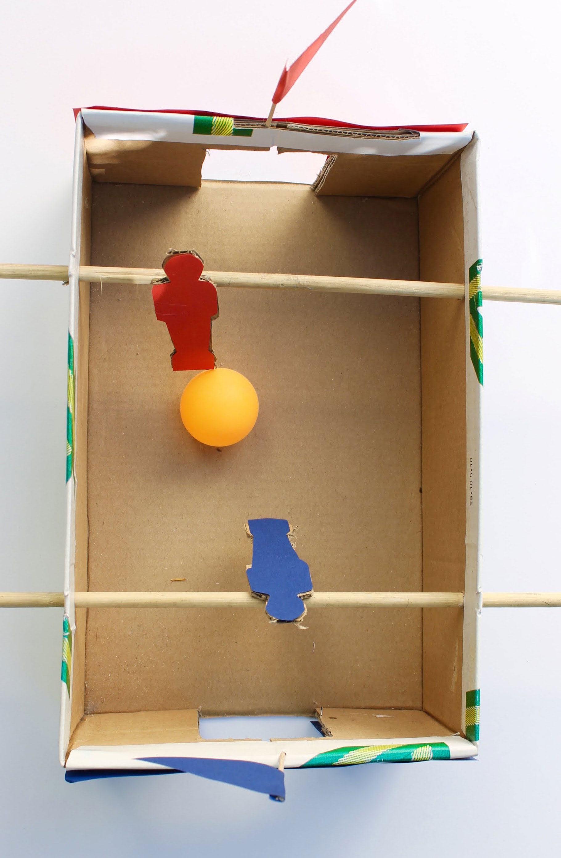 Jogo de pebolim simples feito com caixa de papelão que pode ser adaptado a caixa de sapato.