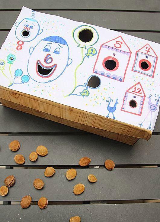 Brincadeira com sementes em encaixes divertidos na tampa da caixa.