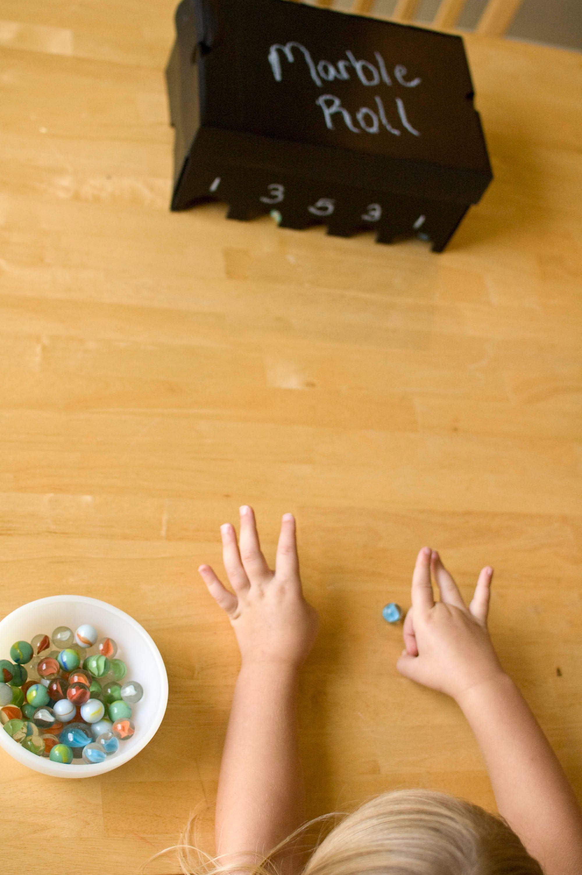 Brincadeira divertida com bolinhas de gude e alvos na caixa de sapato.