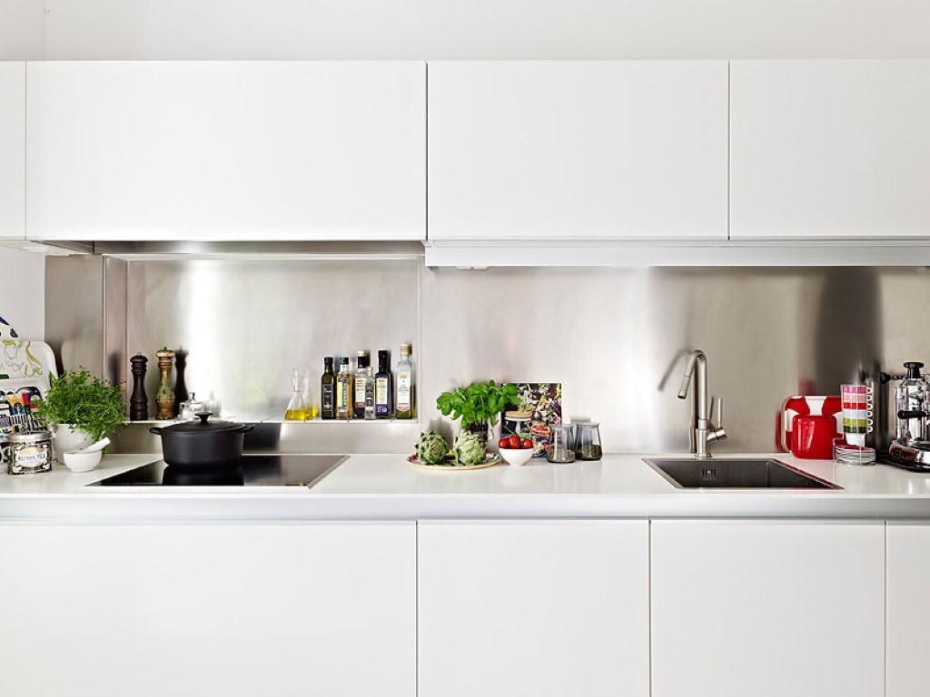 O acabamento em inox da parede combina com os equipamentos da cozinha