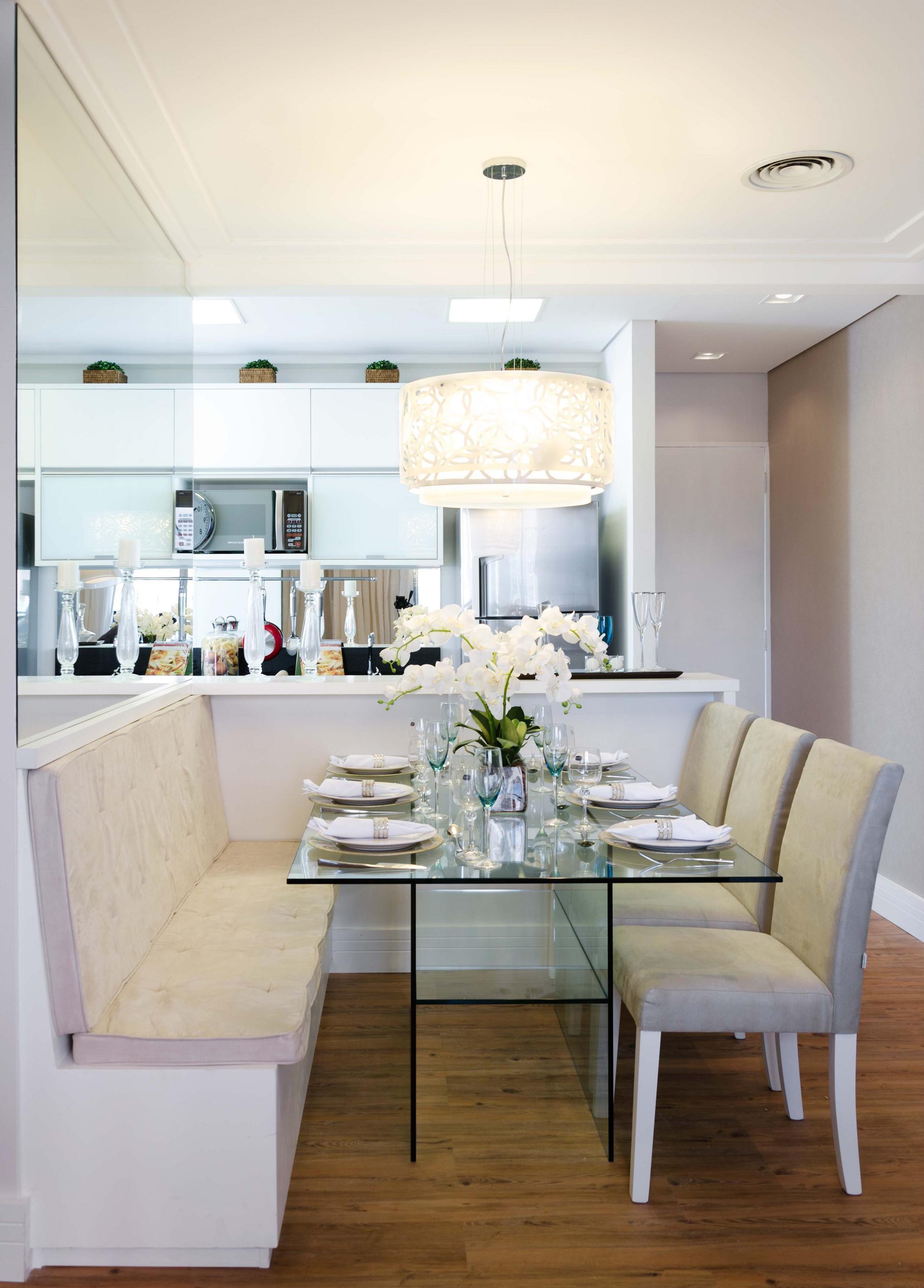 Além da cozinha branca, a sala de jantar complementa com elementos leves como o vidro e o espelho