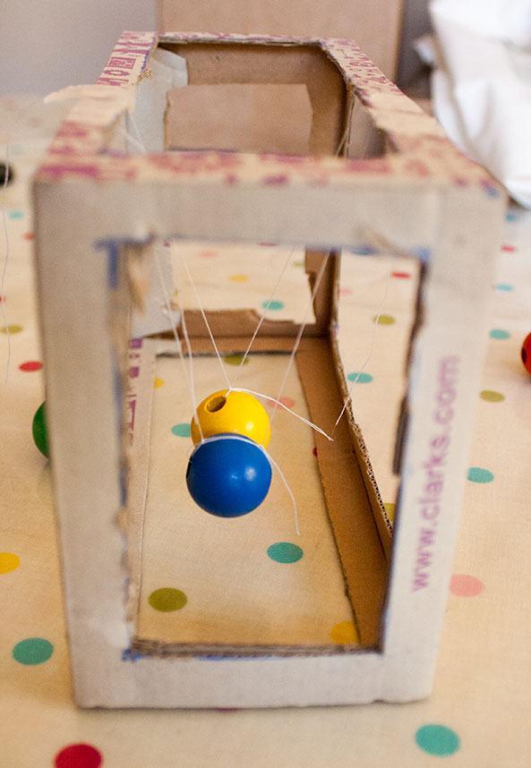 Brinquedo com bolinhas suspensas fixadas na caixa.