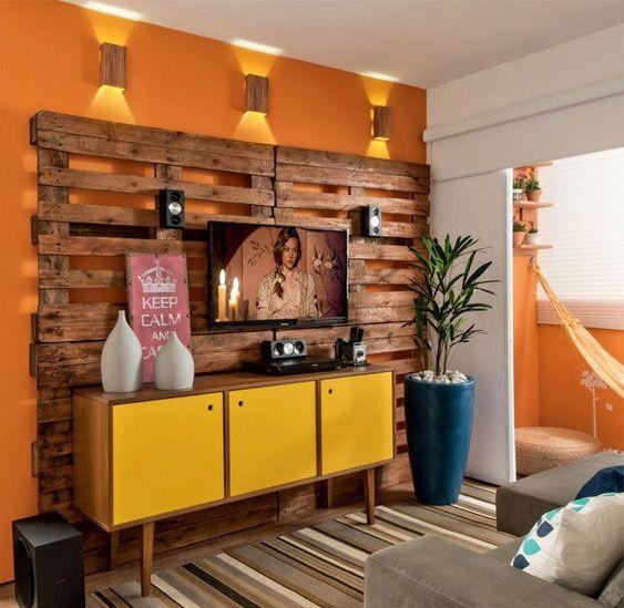 Uma opção é transformar o painel tradicional em um mural de pallets e compor com um rack da mesma tonalidade da madeira.