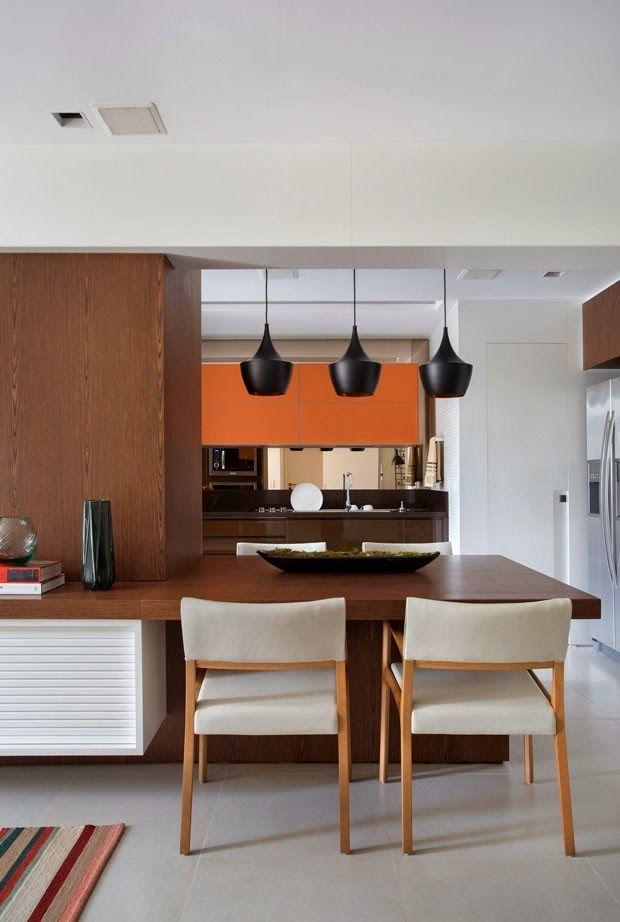 O laranja chega para vibrar e destacar essa cozinha marrom.