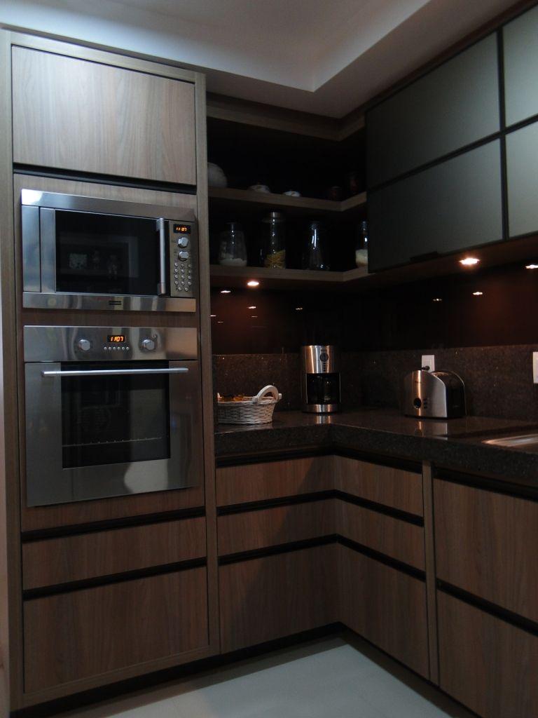 Cozinha com marcenaria marrom e bancada preta.