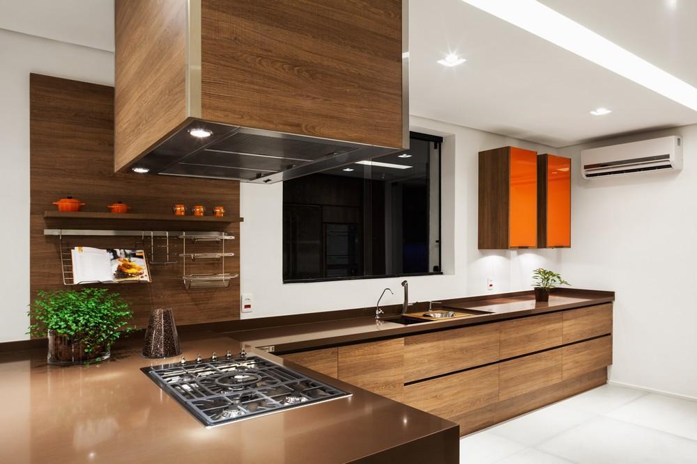 Cozinha em L com decoração marrom e laranja.