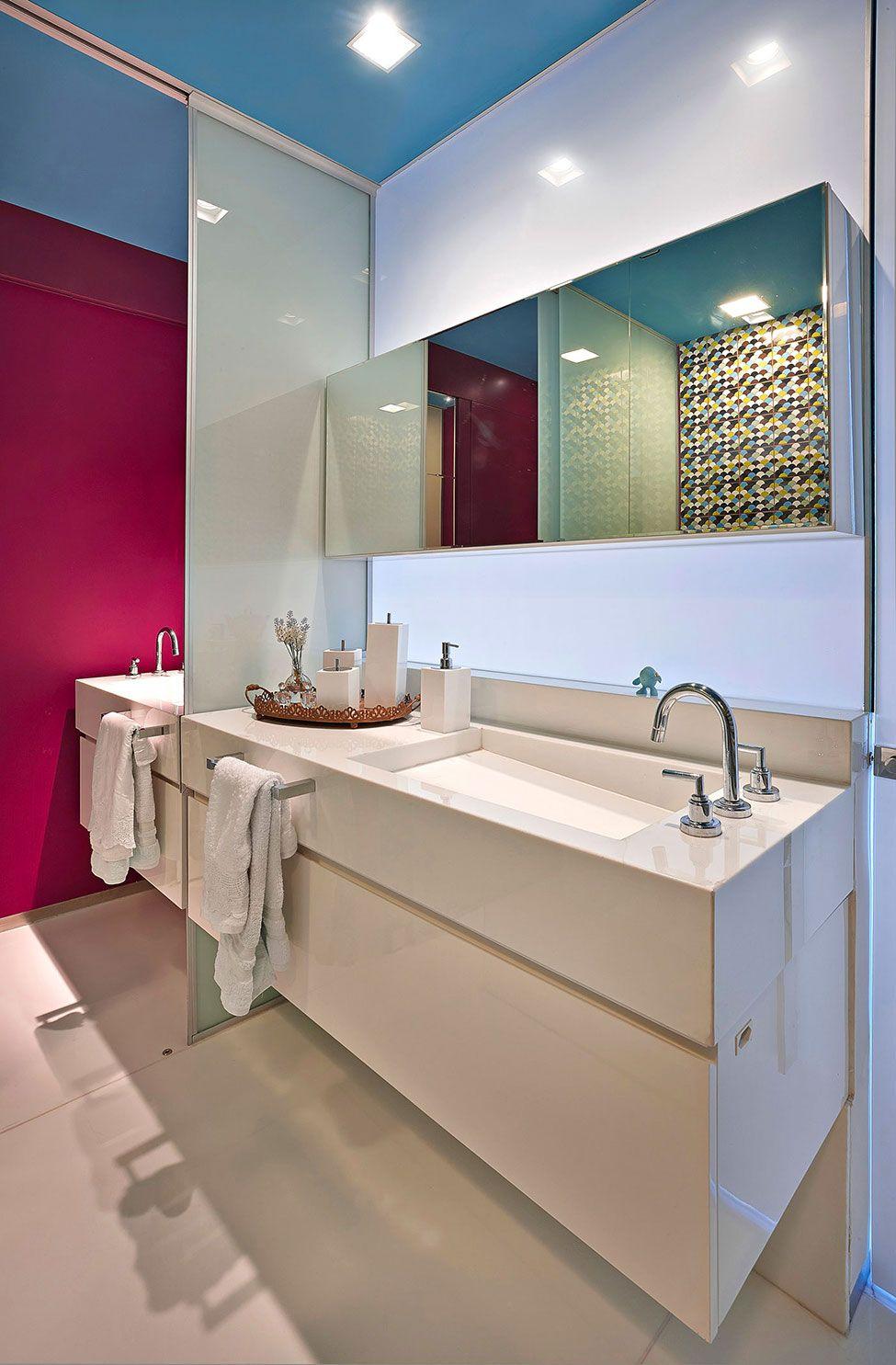 O gabinete com acabamento laqueado se camufla com a bancada lisa branca, formando uma composição única e clean.