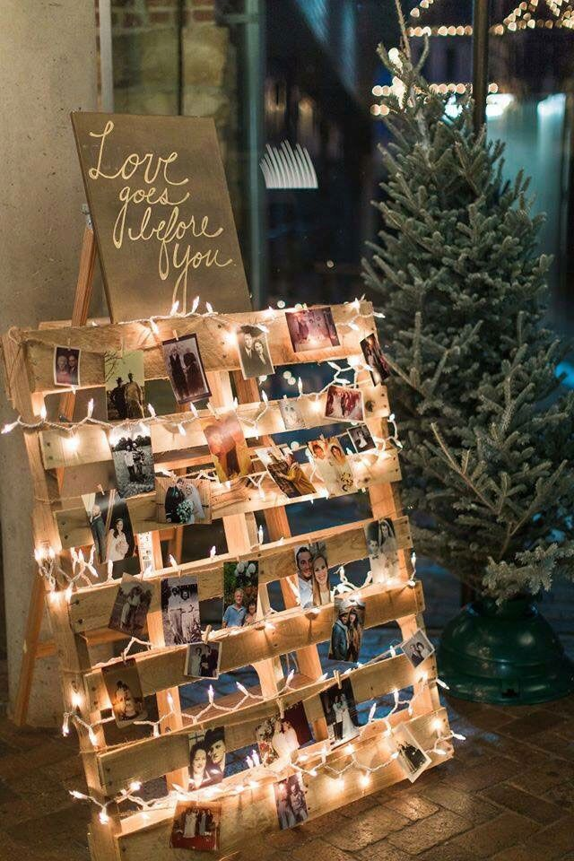 Painel de fotos com pallet de madeira e fio de luzes na decoração de casamento simples