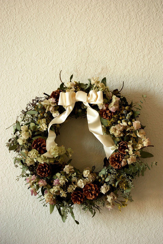 Guirlanda com pinhas, flores e laço creme