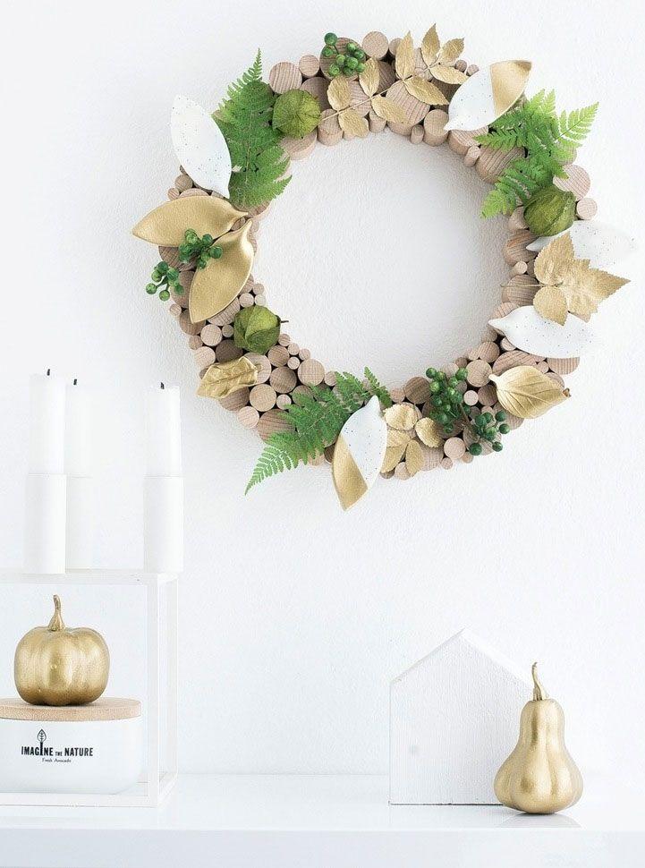 Guirlanda delicada que combina a madeira com tons dourados das folhas