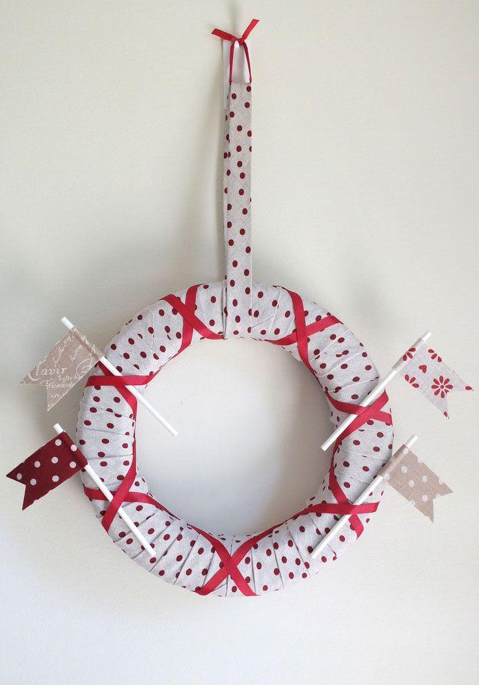 Modelo com fitas de tecido branco com bolinhas vermelhas enroladas ao redor da guirlanda