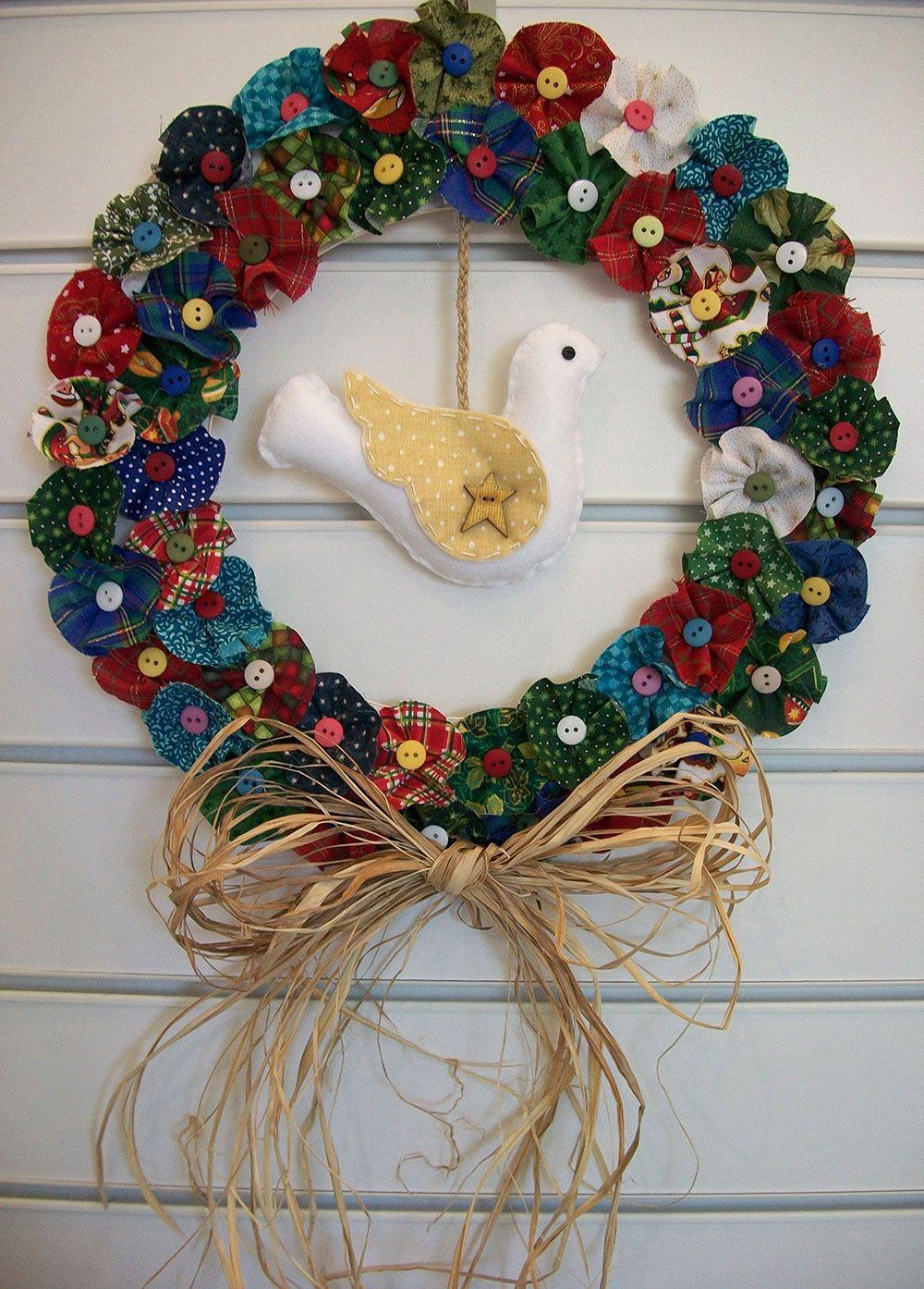 Modelo de guirlanda com flores de tecidos de diferentes estampas e botões
