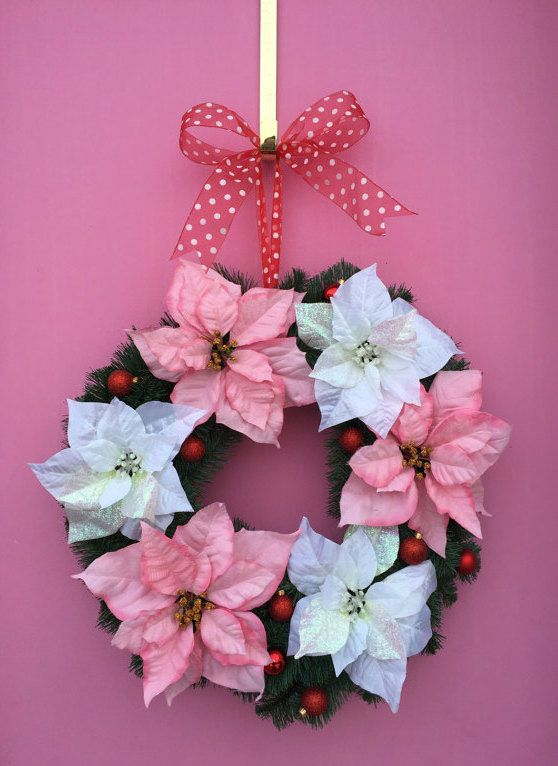 Guirlanda feminina com flores rosa e azul, suspensa por fita vermelha com bolinhas brancas