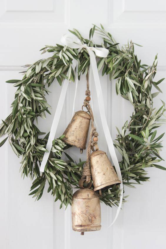 Guirlanda com folhas, laço branco e conjunto de sinos presos por corda