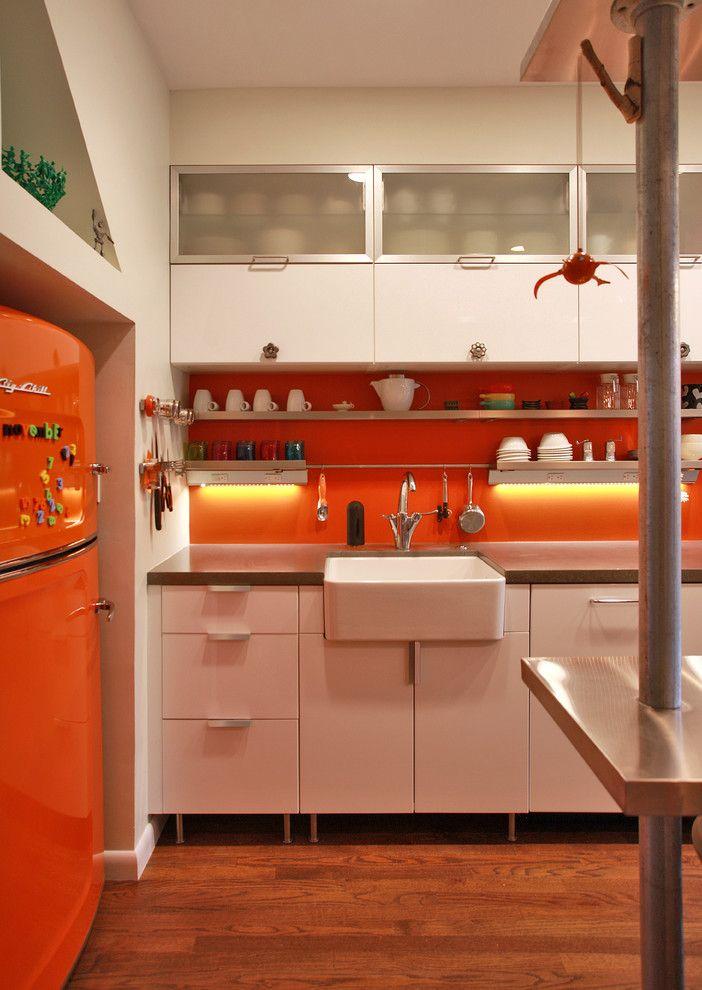 Cozinha que combina o laranja da geladeira com o revestimento acima da bancada