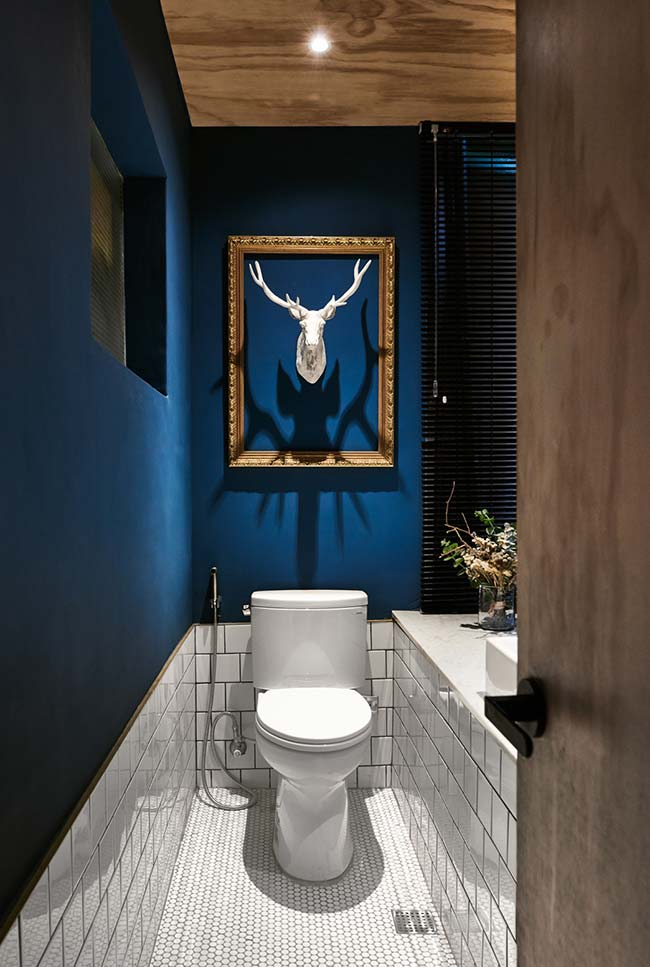 Estátua de cabeça de cervo decora esse banheiro que mescla estilo rústico com tendências atuais de decoração rústica