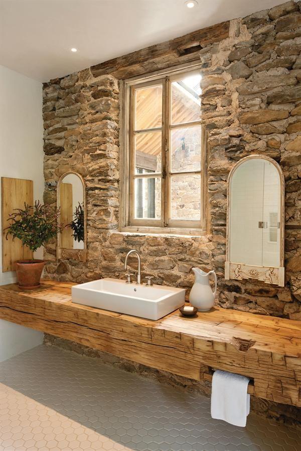 Banheiro decorado com parede de pedras e uma bancada de madeira rústica