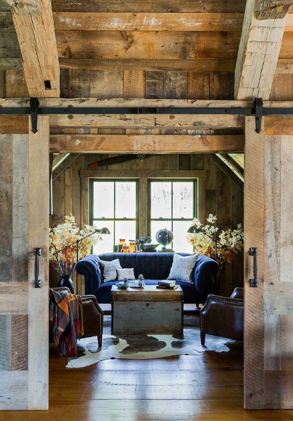 Tons amadeirados predominam na decor rústica, mas o sofá azul dessa sala se sobressai