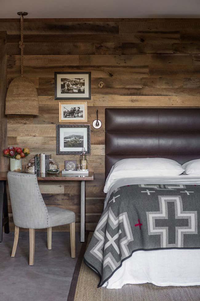 Cabeceira de couro, parede revestida com madeira, luminária de vime e no chão, cimento queimado: receita para um quarto rústico e aconchegante