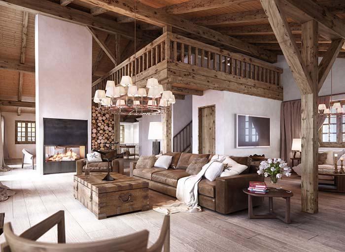 Sofá de couro e mala como centro de mesa são o grande destaque dessa sala com decoração rústica