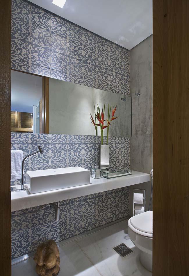 Banheiro marcado pelo contraste entre o cimento queimado e o azulejo português
