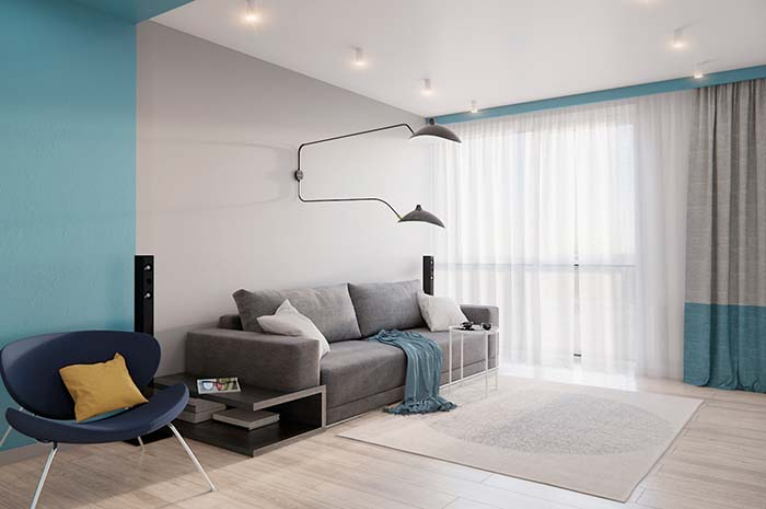 O azul predomina suavemente nessa sala: no cortineiro, no barrado da cortina e na parede