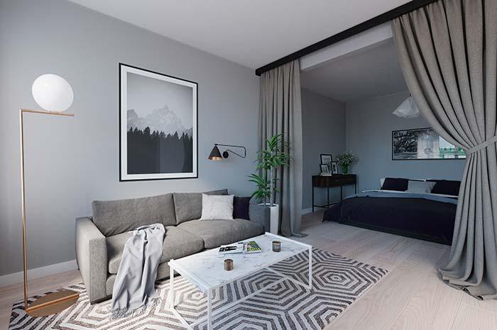 Nessa sala, o cortineiro preto se destaca, já a cortina cinza, em harmonia com a decoração, funciona como uma divisória entre os ambientes