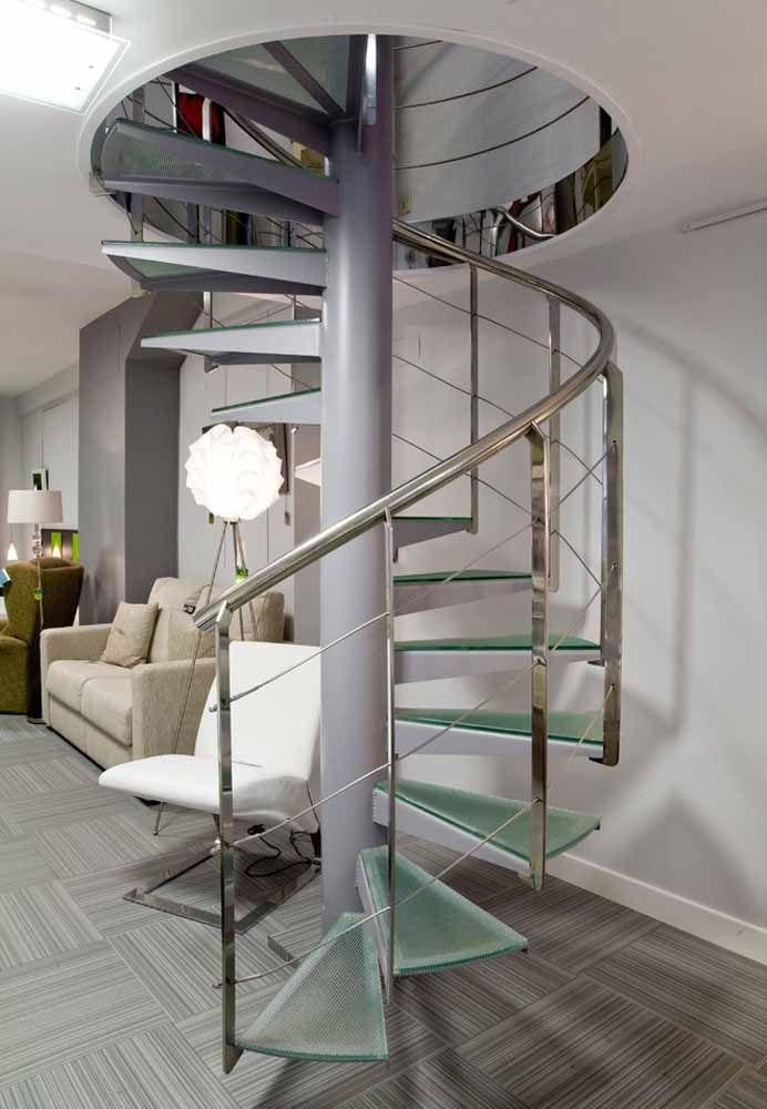 Guarda-corpo metálico e degraus em vidro nesta escada caracol