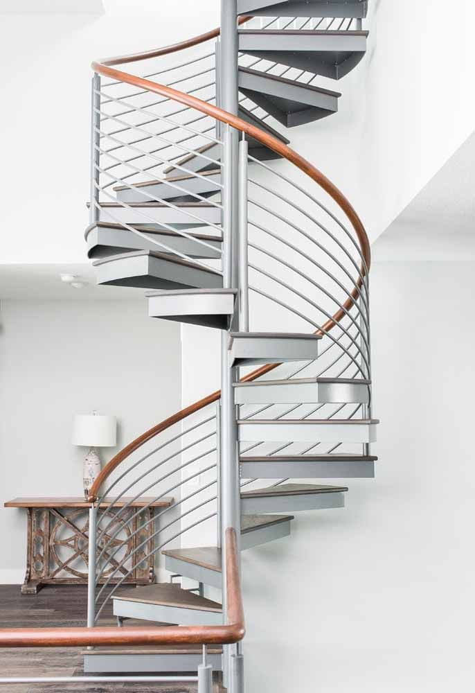 Escada caracol com detalhe no corrimão em madeira e piso que segue o mesmo material do primeiro pavimento