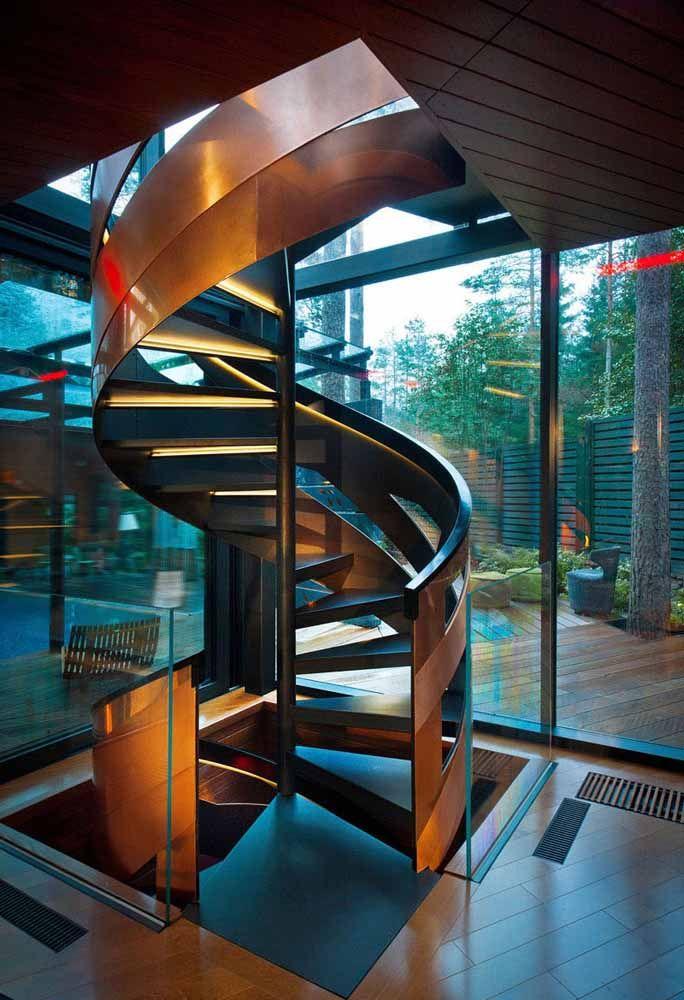 Estrutura lateral vazada com acabamento cobreado confere modernidade a este projeto de escada caracol posicionada na lateral da construção com paredes de vidro