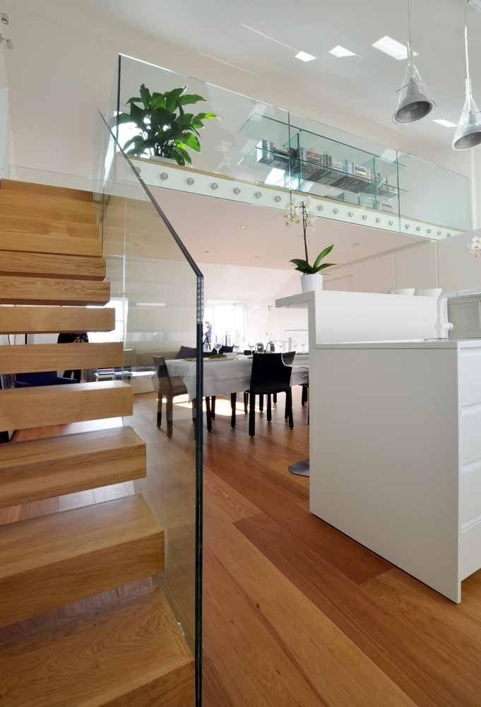 A mistura da transparência com a madeira para deixar a escada com um ar elegante.