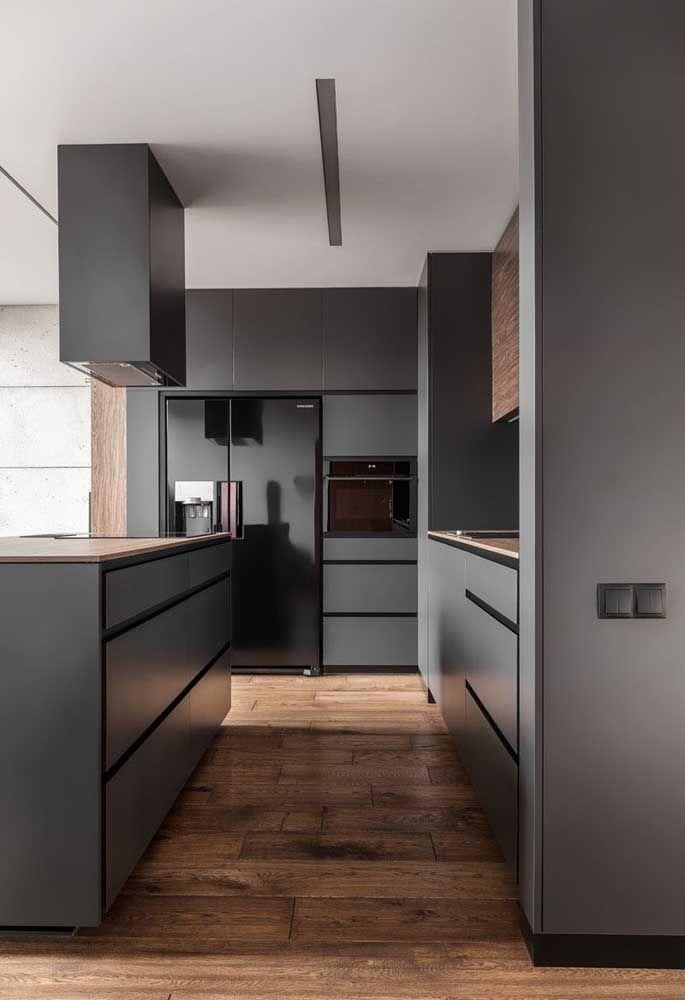 A cor cinza escura combina perfeitamente com os eletrodomésticos da cozinha. Mas é o contraste com o piso de madeira que faz o ambiente ficar mais charmoso.