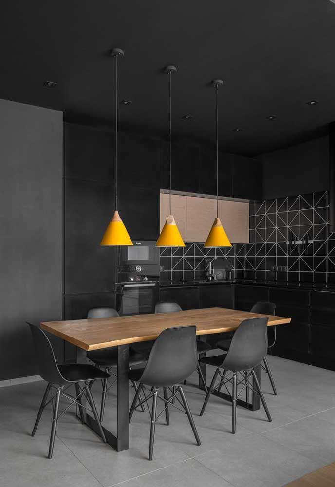 Para quem deseja ter um cômodo mais moderno, pode optar pela cor preta na hora de decorar a cozinha do piso ao teto. É interessante usar uma cor chamativa em alguns elementos decorativos como as luminárias.