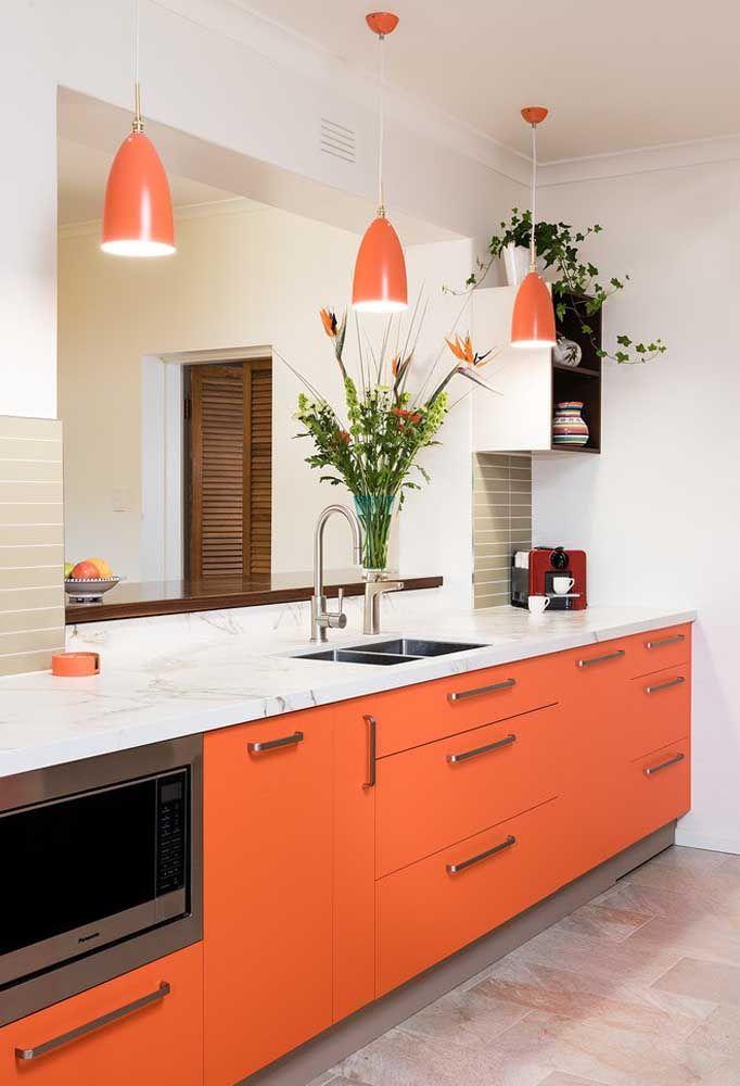 Olha o charme que fica uma cozinha com os móveis no tom salmão. O detalhe fica por conta das luminárias que combinam com os armários.
