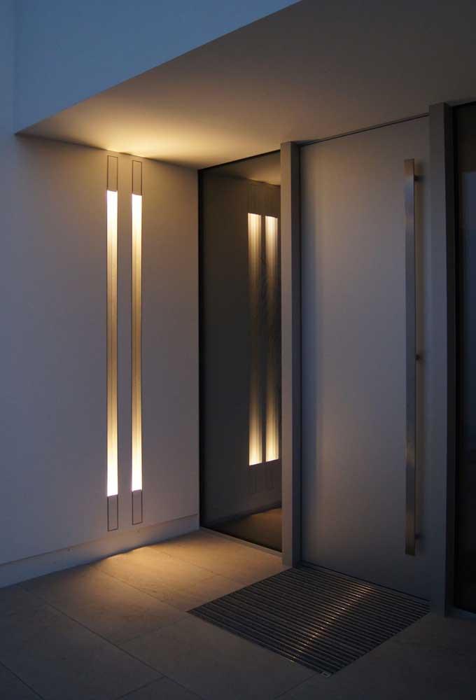 Arandela externa moderna na entrada da casa com design em linhas e iluminação degradê