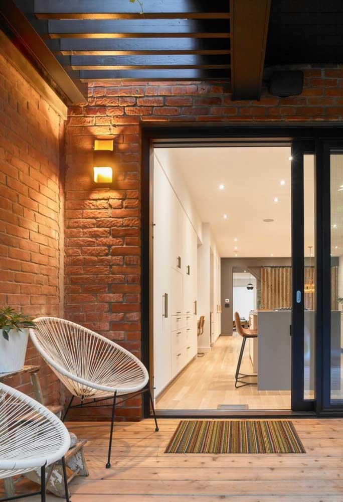 O modelo dessa arandela externa combinou bem com o estilo rústico da parede da casa
