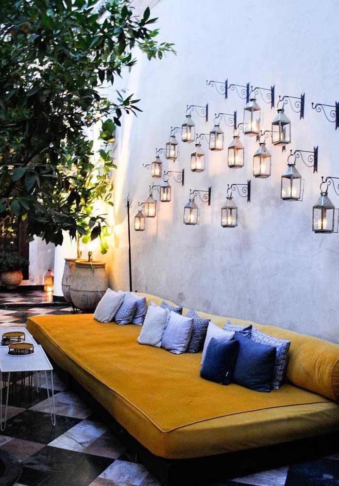 Lindas arandelas externas de ferro em estilo provençal instalada com ganchos no muro da casa; a aplicação de várias peças encheu o espaço de graciosidade