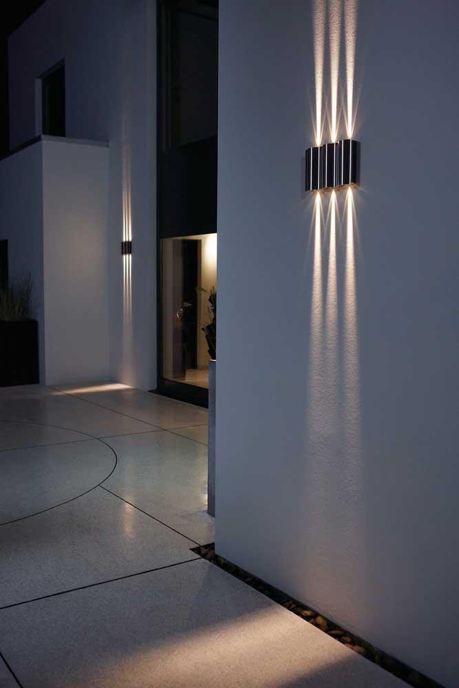 Arandelas externas modernas; esse formato libera a iluminação em dois fachos – para cima e para baixo – com três pontos focais