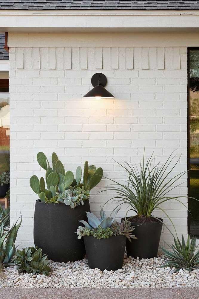 Arandela externa rústica, em ferro; perceba que a iluminação é sutil e focal para o pequeno jardim