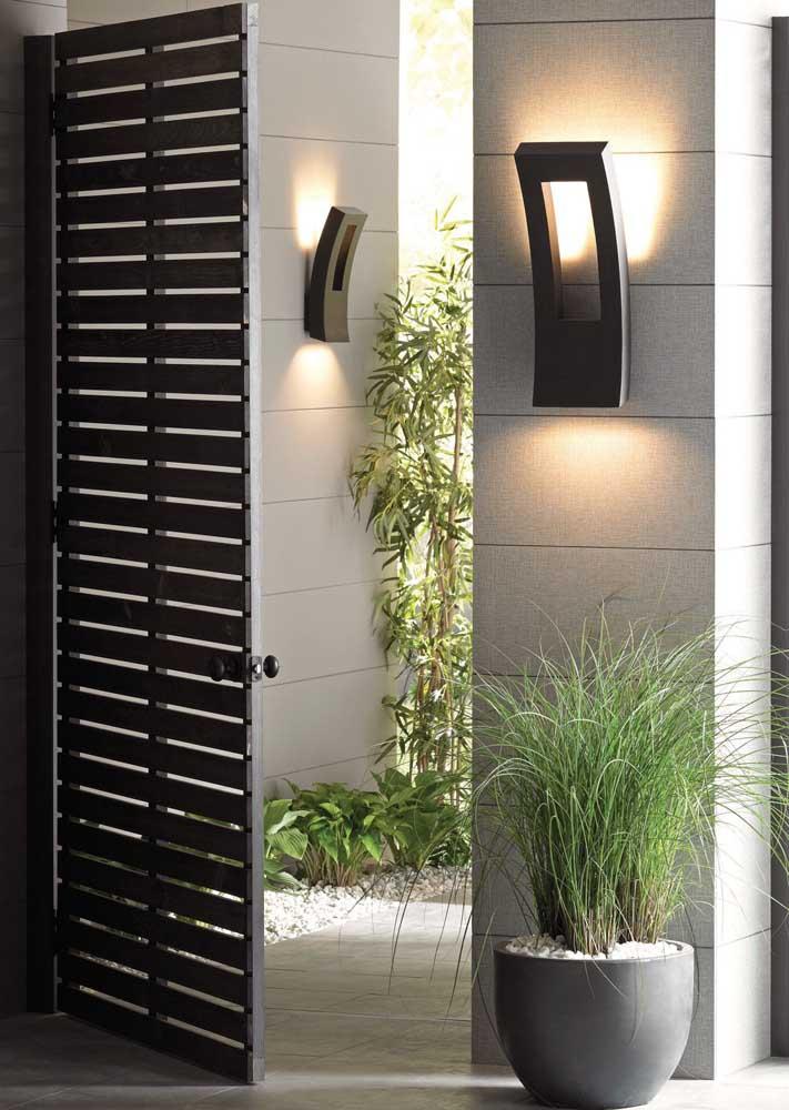 Arandela externa moderna em formato curvilíneo com iluminação voltada diretamente para a parede
