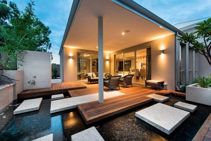 As arandelas garantem o clima aconchegante e acolhedor dessa casa com lago artificial