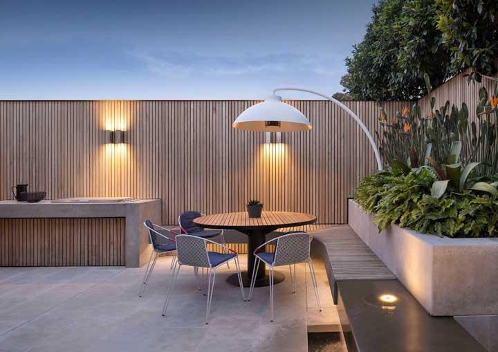 Nessa área externa, arandelas e luminária de chão reforçam a iluminação