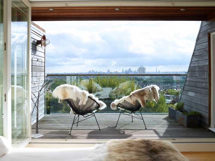 A varanda aberta ganhou uma arandela em ferro com ponto focal aberto para todo o ambiente em madeira
